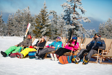 friends sitting with deck chairs in winter mountains. Sunbathing in snow