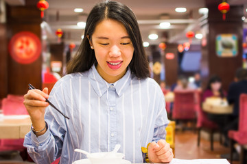 Asian woman enjoying Chinese food in Chinese restaurant