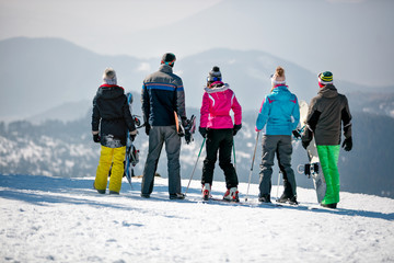 snowboarders enjoy the snow-white scenery of mountains and forests of the mountain top. Back view