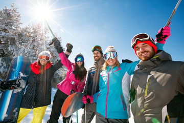 smiling skier's friends in snow mountains