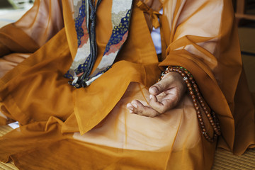 Close up of Buddhist monk wearing golden robe sitting cross legged on the floor, meditating, Buddhist hand gesture.