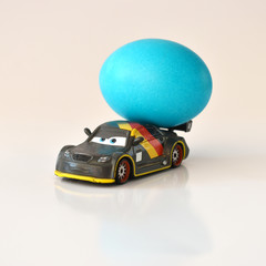 Easter egg on toy car over white background.