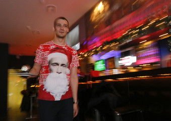 A waiter, wearing a T-shirt with an image of Russian President Putin dressed as Santa Claus, works at a coffee bar in Krasnoyarsk