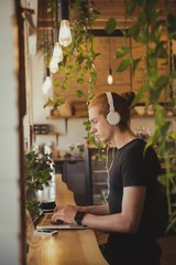 Young man listening to music on headphones while using laptop