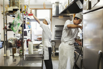 Two chefs working in the kitchen of a Japanese sushi restaurant.