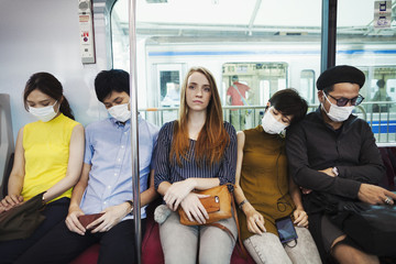Five people wearing dust masks sitting sidy by side on a subway train, Tokyo commuters.