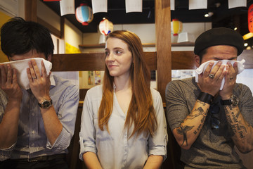 Three smiling people, woman and two men, sitting side by side at a table in a restaurant, men wiping their faces with wet towels.