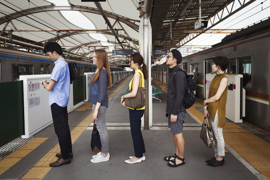 Five people standing in a row on a subway platform, waiting in line, Tokyo commuters.