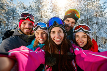 friends skiers on winter holidays taking photo with mobile phone