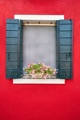 Window with green shutters and pink flowers in the pot. Italy, Venice, Burano