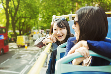 Two smiling women with black hair sitting on the top of an open Double-Decker bus driving along tree-lined urban road.