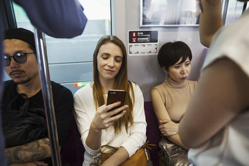 Three people sitting sidy by side on a subway train, Tokyo commuters.