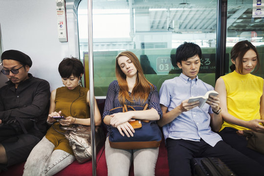 Five people sitting sidy by side on a subway train, Tokyo commuters.