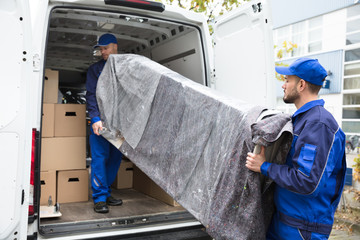 Two Delivery Men Unloading Furniture From Vehicle