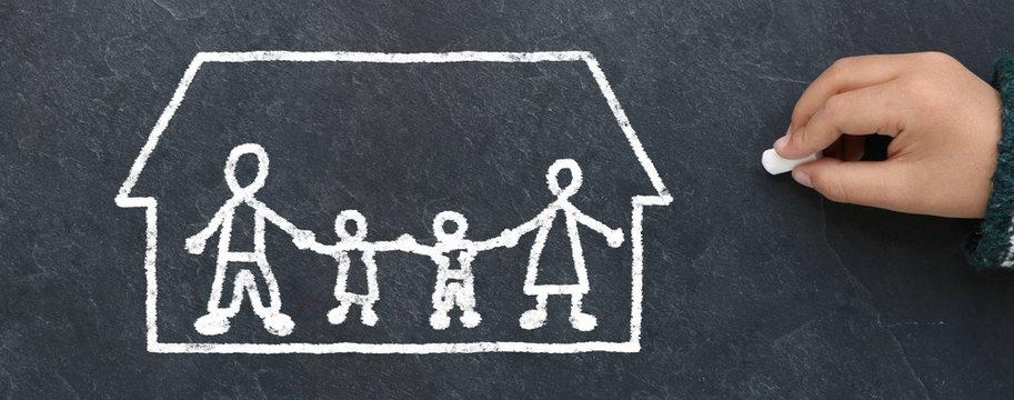 Enfant dessinant une famille dans une maison à la craie sur une ardoise
