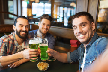 friends with green beer taking selfie at pub