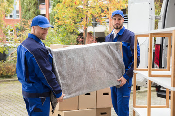 Two Male Worker Unloading Furniture From Truck