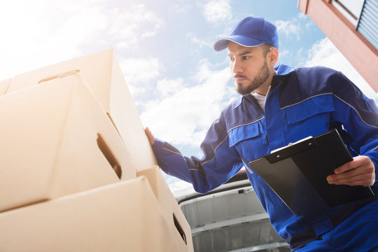 Male Worker Standing Near Cardboard Box Holding Clipboard