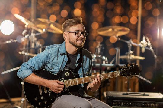musician playing guitar at studio over lights