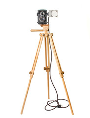 Old Soviet camera on a wooden tripod with a lamp isolated on a white background