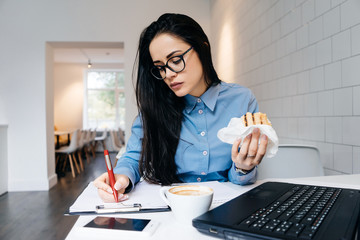 busy young business woman in glasses working in a cafe, writing in a notebook and having a sandwich