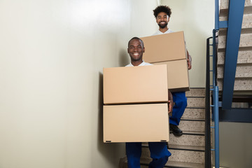 Portrait Of Two Movers Holding Cardboard Boxes