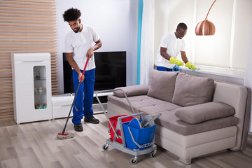 Smiling Two Young Male Janitor Cleaning The Living Room