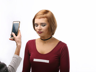 Model with perfect makeup is photographed on smartphone. Beautiful woman. Selfie.