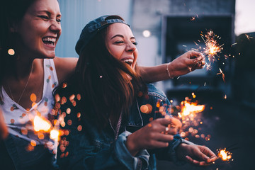 Young adult girlfriends celebrating with sparklers at night