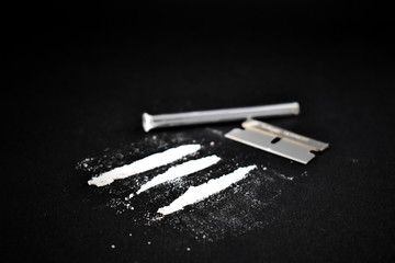 Cocaine line on a black background. Drugs still life. Drug, blade and snort tube. Drug accessories