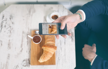 Taking a picture of breakfast, croissant, coffee and chocolate