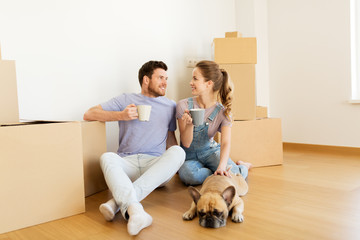 happy couple with boxes and dog moving to new home