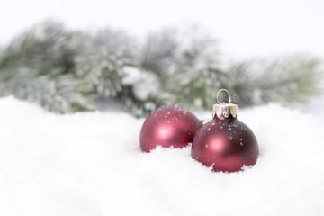 roter Christbaumschmuck im Schnee vor Tannengrün