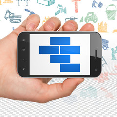Construction concept: Hand Holding Smartphone with  blue Bricks icon on display,  Hand Drawn Building Icons background, 3D rendering