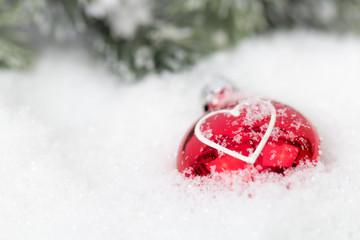 roter Christbaumschmuck mit Herz im Schnee vor Tannengrün