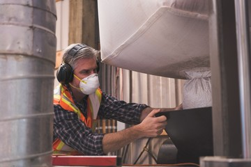 Man in protective workwear refining grain
