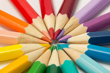 A group of pencils folded in rainbow colors in a circle on a white background
