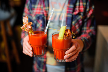 guy is holding two glasses of alcoholic cocktail Bloody Mary