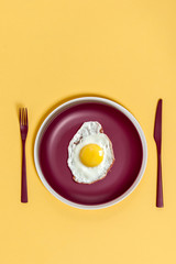 Scrambled eggs on a maroon dish with burgundy cutlery on a light yellow background..