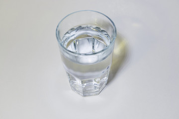 A tall glass of water on white.