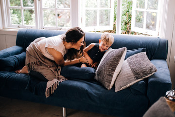 Happy Mother and toddler cuddling on couch at home