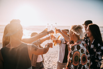 Young friends enjoying beer at beach party