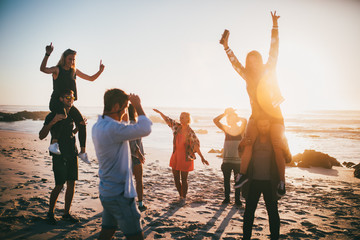 Group of happy friends dancing at beach party