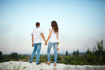 Loving young couple at sunset in the evening on a blurry beautiful background
