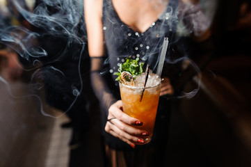 girl is holding an alcoholic orange cocktail with ice and a twig of dry and fresh mint