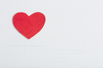 red paper heart on white wooden background