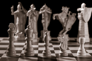 Classic white chess pieces and the same pieces in the form of medieval figures on the background
