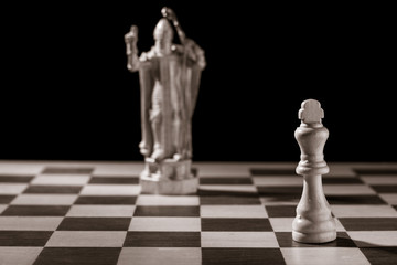 Classic white king and the same chess piece in the form of medieval figure on the background