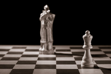 Classic white queen and the same chess piece in the form of medieval figure on the background