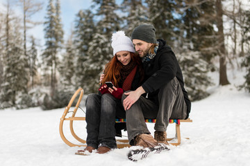 Winter couple busy in looking at mobile screen together